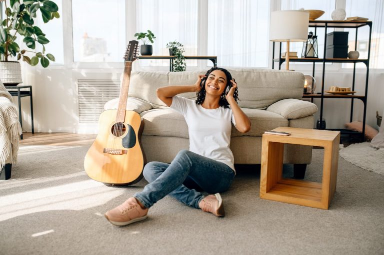 smiling-woman-in-headphones-guitar-on-background-tfdxzj3